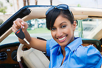 Young Woman Holding Key to Convertible