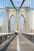 The pedestrian walkway on the  Brooklyn Bridge between Manhattan and Brooklyn over the East River. New York
