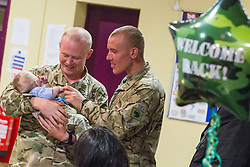© Licensed to London News Pictures . 25/04/2013. Catterick Barracks , North Yorkshire , UK .  Dad Kingsman Daniel Adamou (22)(left) holding his 4 month old son Alfie Adamou . Soldiers from the 1st Battalion , the Duke of Lancaster's Regiment (1 Lancs) arrive at Catterick Barracks to be greeted by their families this evening (Thursday 25th April), following a six month tour in Lashkar Gah , Helmand Province , Afghanistan . With the UK combat mission due to complete by the end of 2014 , this is likely to be the last deployment by 1 Lancs in Afghanistan , the British Army reports . Photo credit : Joel Goodman/LNP