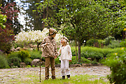 Cute brother and sister in rural chic forest fashion clothing in a forest setting.