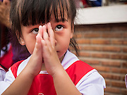 "23 JUNE 2015 - MAHACHAI, SAMUT SAKHON, THAILAND:  School children pray during the City Pillar Shrine Procession in Mahachai. The Chaopho Lak Mueang Procession (City Pillar Shrine Procession) is a religious festival that takes place in June in front of city hall in Mahachai. The ""Chaopho Lak Mueang"" is  placed on a fishing boat and taken across the Tha Chin River from Talat Maha Chai to Tha Chalom in the area of Wat Suwannaram and then paraded through the community before returning to the temple in Mahachai.    PHOTO BY JACK KURTZ"