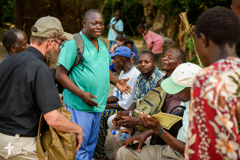 Sierra Leonean nurse and pastor Stephen Ngaujah talks with fellow members of the Christ Evangelical Lutheran Church—Sierra Leone (CELC—SL) following the fourth day of the LCMS Mercy Medical Team on Thursday, May 10, 2018, in the Yardu village outside Koidu, Sierra Leone, West Africa. LCMS Communications/Erik M. Lunsford