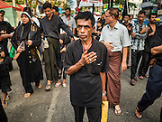 23 OCTOBER 2015 - YANGON, MYANMAR:  Men beat their chests and pray during an Ashura procession in Yangon. Ashura commemorates the death of Hussein ibn Ali, the grandson of the Prophet Muhammed, in the 7th century. Hussein ibn Ali is considered by Shia Muslims to be the third imam and the rightful successor of Muhammed. He was killed at the Battle of Karbala in 610 CE on the 10th day of Muharram, the first month of the Islamic calendar. According to Myanmar government statistics, only about 4% of the population is Muslim. Many Muslims have fled Myanmar in recent years because of violence directed against Burmese Muslims by Buddhist nationalists.   PHOTO BY JACK KURTZ