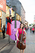 08/09/2014 Repro Free , Sarah Joyce, cellist   with Beau Holland, stiltwalkerat the launch of Music for Galway's 34th International Concert Season on Quay Strret Galway.  <br /> Picture:Andrew Downes