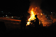 Firefighter extinguish a large bonfire during the lag b'omer celebrations (Lag B'Omer is a day for bonfire celebrations.)