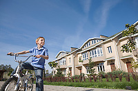 Boy stands with bicycle in new housing development
