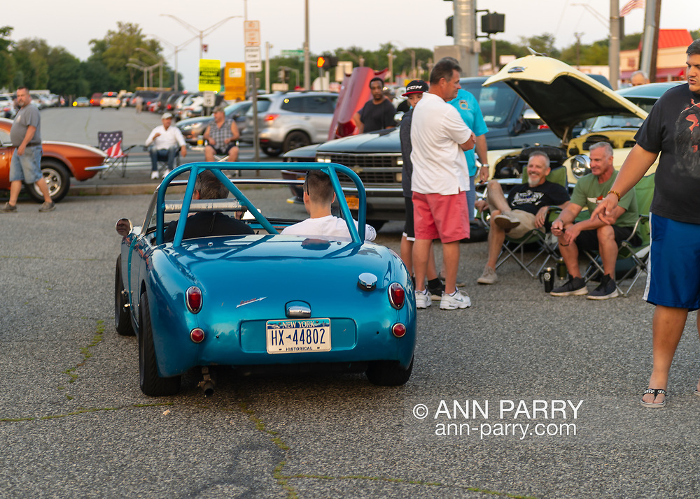 Bellmore, New York, USA. August 24, 2018. Two men ride in metallic blue Austin Healey Sprite as others look at the small historical car at Bellmore Friday Night Car Show, in parking lot of LIRR Bellmore station. This traditional Long Island event is hosted by the Chamber of Commerce of the Bellmores.