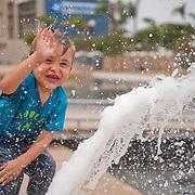 a little boy ecstatically slapping water from a waterjet, as waterdrops envelop him