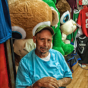 Amusement Arcades Barker with Stuffed Prize Animals. <br />