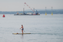 © Licensed to London News Pictures. 19/09/2016. Portsmouth, UK.  A man on a paddle board making the most of calm conditions and passing the installation works for new navigation light piles, which are being installed for the Queen Elizabeth Class Carriers in the Solent this morning, 19th September 2016. The weather is set to be cloudy with sunny intervals in the south east of England. Photo credit: Rob Arnold/LNP