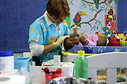 A nurse is applying ear disinfectant to a young girl at the Thembacare HIV care hospice in Athlone, Cape Town.