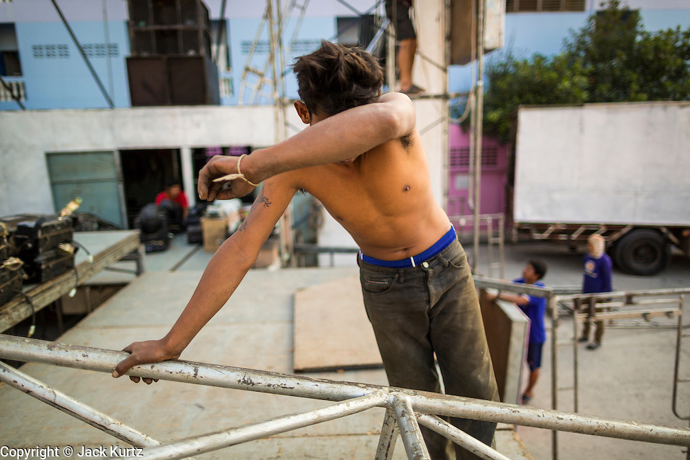 19 JANUARY 2014 - BANGKOK, THAILAND:  A member of the crew wipes his brow while hauling stage rigging across an under construction stage before a mor lam in Khlong Tan Market in Bangkok. Mor Lam is a traditional Lao form of song in Laos and Isan (northeast Thailand). It is sometimes compared to American country music, song usually revolve around unrequited love, mor lam and the complexities of rural life. Mor Lam shows are an important part of festivals and fairs in rural Thailand. Mor lam has become very popular in Isan migrant communities in Bangkok. Once performed by bands and singers, live performances are now spectacles, involving several singers, a dance troupe and comedians. The dancers (or hang khreuang) in particular often wear fancy costumes, and singers go through several costume changes in the course of a performance. Prathom Bunteung Silp is one of the best known Mor Lam troupes in Thailand with more than 250 performers and a total crew of almost 300 people. The troupe has been performing for more 55 years. It forms every August and performs through June then breaks for the rainy season.              PHOTO BY JACK KURTZ