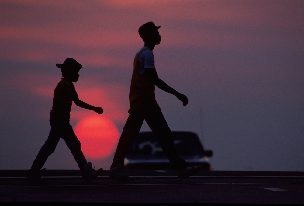 A silhouetted man and a boy in synchronization as they walk with the sun setting behind them.