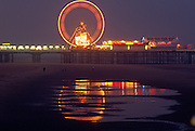 The blurred lights of Blackpool's south pier register as a circle in this time exposure. Reflected on the puddles in beach sand, we see the colours of this iron structure on England's north west coast. Work began to build the pier in 1892. It was constructed, at a total cost of £50,000. .South Pier (originally known as Victoria Pier) is one of three piers in Blackpool, England. Located on South Promenade on the South Shore, the pier contains a number of amusement and adrenalin rides. It opens each year from March to November and is owned by Six Piers Limited.