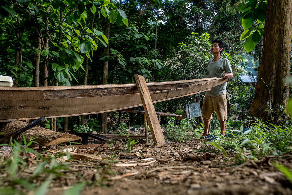 A man builds a boat in the village of Khoc Kham, which is located on the banks of the Mekong river. The village is not connected to the main electrical grid and many residents operate their own turbines to power lights and sometimes small appliances.