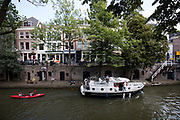 In Utrecht varen mensen in een motorboot en een kano door de Oudegracht.<br /> <br /> In Utrecht tourists are sailing at the Oudegracht.