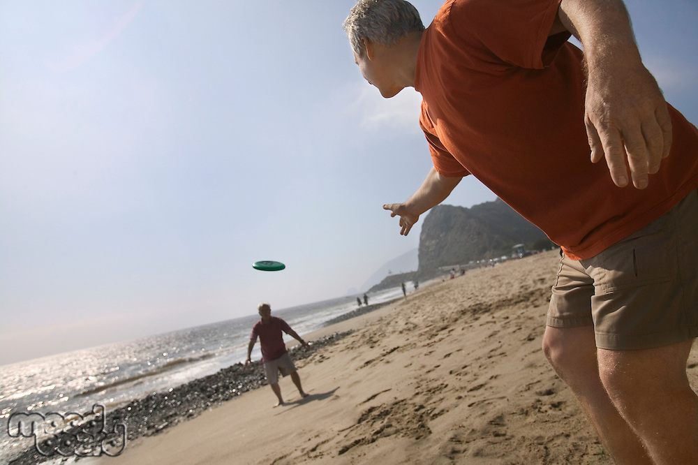 Two Friends Throwing Frisbee on Beach