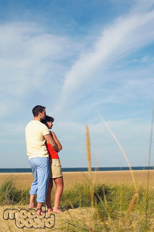 Couple on Beach Looking at Ocean