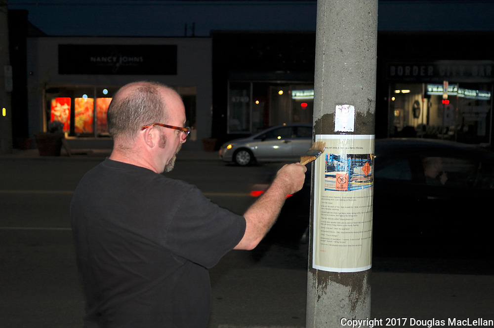 """CANADA, Windsor. May, 2017. Jeff Noonan, acedemic and artist,  puts up posters from the collaborative art piece """"Stories to the Streets"""" in Pillette Village and the Seminole and George area. """"Stories"""" is an exhibition in the MayWorks Windsor 2017 labour arts festival."""