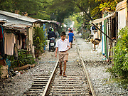 04 FEBRUARY 2015 - BANGKOK, THAILAND: A boy on his way to school walks along railroad tracks in a working class neighborhood in Bangkok. After months of relative calm following the May 2014 coup, tensions are increasing in Bangkok. The military backed junta has threatened to crack down on anyone who opposes the government. Relations with the United States have deteriorated after Daniel Russel, the US Assistant Secretary of State for Asian and Pacific Affairs, said that normalization of relations between Thailand and the US would depend on the restoration of a credible democratically elected government in Thailand.    PHOTO BY JACK KURTZ