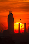 UNITED KINGDOM, London: 19 April 2018 The sun rises behind the chimneys of Battersea Power Station this morning on what will be yet another warm day. Londoners will be enjoying the weather again today as high temperatures are set to continue in the capital. Rick Findler / Story