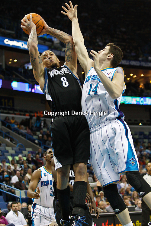 February 7, 2011; New Orleans, LA, USA; Minnesota Timberwolves power forward Michael Beasley (8) rebounds over New Orleans Hornets power forward Jason Smith (14) during the second quarter at the New Orleans Arena.   Mandatory Credit: Derick E. Hingle