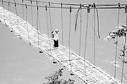Woman crossing river on wooden suspension bridge