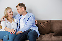 Loving mid adult couple sitting on sofa at home