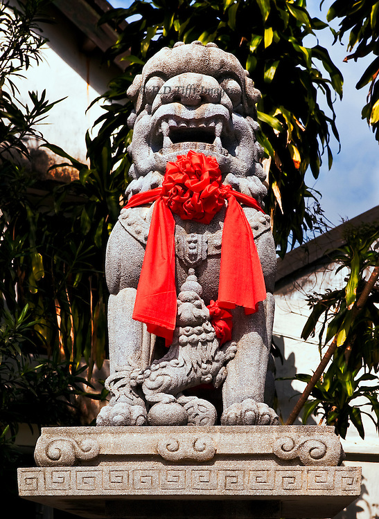 Life sized stone or concrete figure of a seated guardian lion wearing a fabric red ribbon, outside a pagoda in Vietnam.  A little dog is between its front paws.