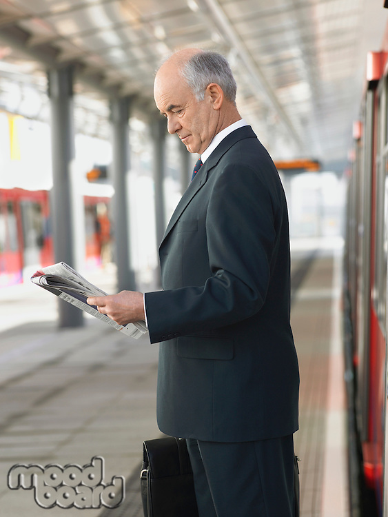 Businessman Reading Newspaper at empty Train Station side view