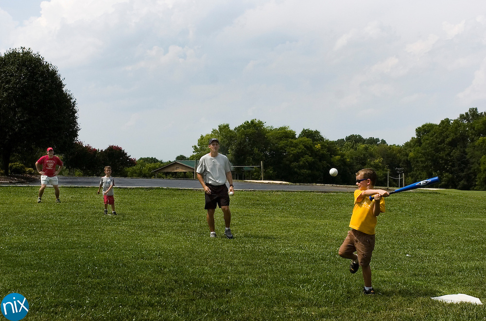 Cole St. Yves, 6, bats while his father Jeff St. Yves pitches during a makeshift game of baseball at Frank Liske Park Tuesday afternoon. Jeff's son Nathan is on second baseb and Jeff's brother Gar St. Ives is behind the base.