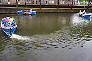 Een groep toeristen vaart in een boot door Utrecht.<br />