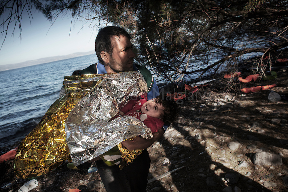 A man walks away with a child from the rubber boat that brought him to Lesbos. Refugees from Afghanistan and Syria arrive in boats on the shores of Lesbos near Skala Skamnias, Greece on 02 November, 2015. Lesbos, the Greek vacation island in the Aegean Sea between Turkey and Greece, faces massive refugee flows from the Middle East countries.