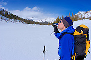 Backcountry skier having a snack and enjoying the view along Lee Vining Creek, Inyo National Forest, Sierra Nevada Mountains, California
