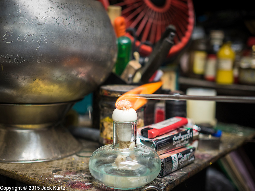 "25 MAY 2015 - BANGKOK, THAILAND: A tattoo needle is sterilized in a flame in Ajarn Neng Onnut's Sak Yant tattoo parlor. Sak Yant (Thai for ""tattoos of mystical drawings"" sak=tattoo, yantra=mystical drawing) tattoos are popular throughout Thailand, Cambodia, Laos and Myanmar. The tattoos are believed to impart magical powers to the people who have them. People get the tattoos to address specific needs. For example, a business person would get a tattoo to make his business successful, and a soldier would get a tattoo to help him in battle. The tattoos are blessed by monks or people who have magical powers. Ajarn Neng, a revered tattoo master in Bangkok, uses stainless steel needles to tattoo, other tattoo masters use bamboo needles. The tattoos are growing in popularity with tourists, but Thai religious leaders try to discourage tattoo masters from giving tourists tattoos for ornamental reasons.       PHOTO BY JACK KURTZ"