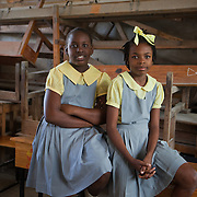 Danaika (L) and Rachelle, pupils at the Pyramide School in Leogane, which was damaged by the earthquake. CARE is supporting the school with water and sanitation programs like building latrines and hand washing stations.