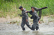 North Korean fishermen walk along the Yalu River in the town of Sunuiju on the DPRK-China border July 9, 2006. After Pyongyang defied world opinion and test-fired seven missiles last week, Japan formally introduced a U.N. resolution, co-sponsored by the United States, Britain and France, to impose sanctions against its missile program.. DPRK, north korea, china, dandong, border, liaoning, democratic, people's, rebiblic, of, korea, nuclear, test, rice, japan, arms, race, weapons, stalinist, communist, kin jong il