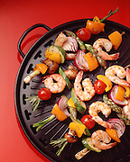 Vegetables and shrimp are skewered with rosemary stems and placed on a black steel griddle on a red background.