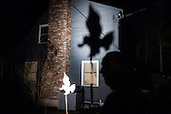 Outside his home in Concord, Vallieres stands near a wooden cutout shaped like a peregrine falcon after a party for Hawk Watch participants on November 15, 2013. He used the cutout to project a silhouette of a peregrine that was visible from the road.