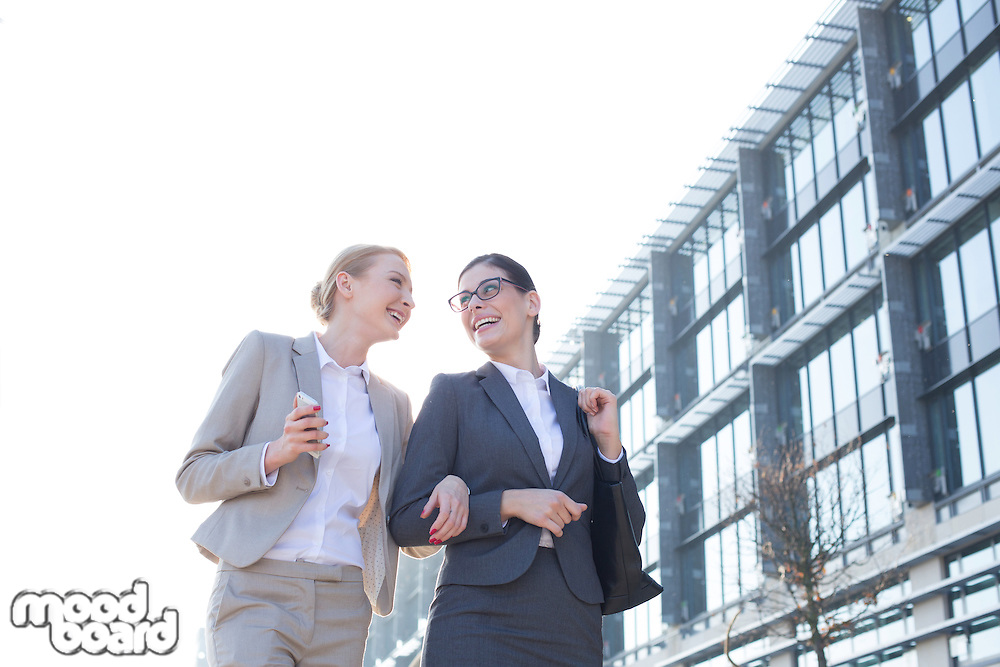 Low angle view of happy businesswomen walking outside office building against clear sky
