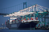 Container cargo ship and industrial shipping cranes at the Port of Los Angeles, Long Beach, California