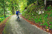 Cyclists exploring the backroads and mixed forest of Plitvice Lakes National Park, Croatia
