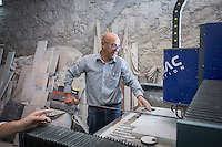 SIRACUSA, ITALY - 8 NOVEMBER 2016: Roberto Gibilisco (60)  prepares the marble that will be engraved by a pantograph for the gravestone of Musaab Shabani, a victim of the August 24th 2014 shipwreck, here at the Gibilisco marble-worker's workshop in Siracusa, Italy, on November 8th 2016.<br /> <br /> Musaab Shabani was buried in the cemetery of Sortino, marked by a gravestone with the number nine because at the time he hadn't been identified yet. He was later identified by his brother Abd thanks to the efforts of policeman Angelo Milazzo. Since then, Abd has arranged to have a gravestone made bearing his brother's name and date and place of birth as well as a religious inscription in Arabic, bringing a final bit of closure to this tragic chapter. <br /> <br /> On August 24th 2014, a boat carrying more than 400 migrants, departed from the coasts of Libya in the attempt to reach Italy, capsized in international waters in the Mediterranean Sea. Rescuers of the Italian Navy saved 352 people, and recovered 24 lifeless bodies.<br /> <br /> Following the events of the Arab Spring in 2011, including Gaddafi's death and Libya's plunge towards chaos, clandestine crossings skyrocketed, as did the number of people drowning. In 2014 over 170,000 arrived in Italy and since then more than 10,000 perished in the Mediterranean sea.<br /> <br /> Only a fraction of these bodies have ever been recovered, and, of the ones that have, the majority remain unidentified. In Sicily alone there are more than 1,500 graves of anonymous refugees and migrants–people from Syria and other war torn countries–who have drowned in shipwrecks at sea.<br /> <br /> Despite the decades long persistence of the problem, Italy has yet to develop a comprehensive approach to handling the bodies of shipwreck victims. Many pieces of a functional body identification system are in place, but its overall effectiveness is crippled by a lack of coordination between the various local agencies involved and national author