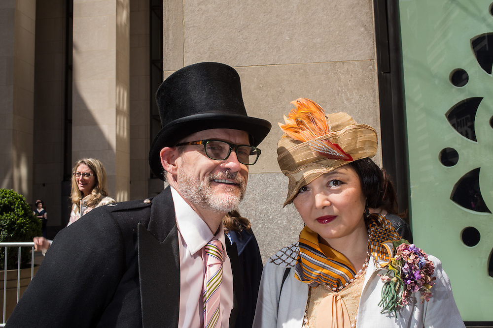 New York, NY, USA-27 March 2016. A couple dressed for the day, he in a top hat, she in a retro-looking feathered hat, on Fifth Avenue in the annual Easter Bonnet Parade and Festival.