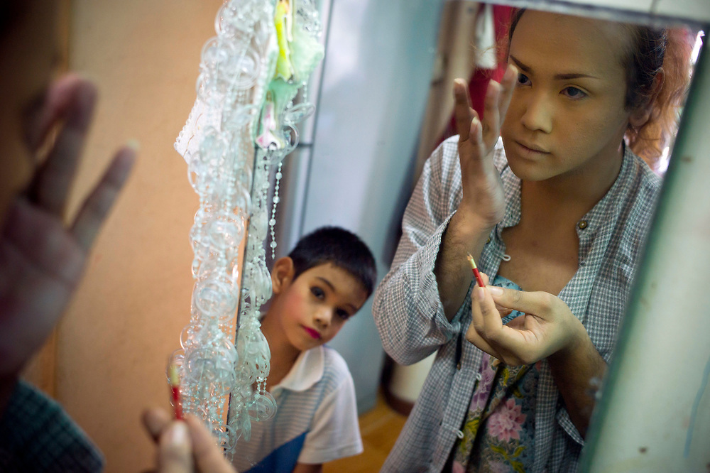 "Bangkok November 13, 2013<br /> Kafille is 6 years old looking at His older brother during a make-up time, Aekachai, 23, ladyboy, and Kafille was definitely influenced by him. His mother had noticed since he was 3 years old, he already behaved as a little girl, showing signs of being feminine. As her mother said: ""we can't do anything, he has to follow his heart and has to live his life the way he wants to""