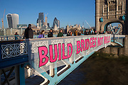 """The Bridges Not Walls movement drop a banner reading """"Bridges Not Walls' from Tower Bridge in London to coincide with banner drops all over the UK sending a clear message to Donald Trump the 45th president of the United States to build bridges not walls on the day of his inauguration. (photo by Andrew Aitchison)"""