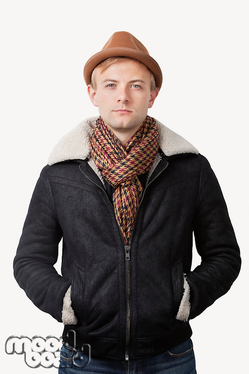 Portrait of young Caucasian man in warm clothing standing against white background