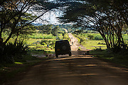 Land Rover 4x4 car drives along a dirt road track towards pedestrians and cyclists on the road to Mbulu, Manyara district, Tanzania, East Africa. (photo by Andrew Aitchison / In pictures via Getty Images)