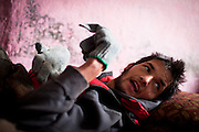 Afghanistan: Kabul: Azis Rahman, a physically disabled 22 year old son of Khalil Rahman lies on the floor of the families one room home, part of a dilapidated warehouse building known as Tamil Mill Bus site, owned by the Ministry of Transportation...Aziz has never been diagnosed because the family know they cannot afford the medical consultation or subsequent treatment. ..Khalil says he is not fit enough to work in manual labour. His sons occasionally sell plastic bags at the markets bringing home 4-50 Afs per day. otherwise they rely on the charity of their neighbours and handouts from NGO's such as WFP and UNHCR...Khalil says he lost his right eye when he and his family were fleeing across the mountains to pakistan from Afghanistan. ..Tajik and Pashtun families live side by side without any major conflict at the Tamil Mill Bus site. Over 70% of the families are returnees from the period 2002-2004 who are unable to achieve sustainable reintegration in their places of origin and subsequently drifted to Kabul City in search of work...There is a nearby school which is accessible to the children but the poor economic circumstances of the many families oblige them to send their children out to work. low levels of literacy, particularly amongst the women, limit their access to employment other than the lowest paid daily wage labor...Afghans returning from exile abroad face many challenges. Security is a major obstacle to return in many districts. Others choose not to return tot heir villages because of landlessness or the lack of job opportunities, fuelling population movements and especially further urbanisation. Impoverished returnees and IDP's living in Kabul cit struggle to meet their daily needs. The attraction of daily wage labour draws growing numbers tot he city. But the rising cost of rental accommodation and basic commodities price them out of the market and relegate them to life in the informal settlements which have mushroomed across the city...While 70-80% o