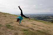 A young girl cartwheels near the summit of The Beacon, on 15th September 2018, in Malvern, Worcestershire, England UK. Worcestershire Beacon, also popularly known as Worcester Beacon, or locally simply as The Beacon, is a hill whose summit at 425 metres (1,394 ft)[1] is the highest point of the range of Malvern Hills that runs about 13 kilometres (8.1 mi) north-south along the Herefordshire-Worcestershire border, although Worcestershire Beacon itself lies entirely within Worcestershire.